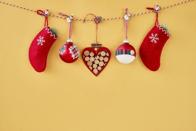 Kerstmis achtergrond. kerst ornamenten, rode kerst sokken en hart opknoping op touw op gouden achtergrond. ruimte kopiëren.