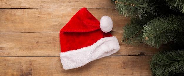 Kerstmis achtergrond. kerstman hoed en takken van een kerstboom op een houten achtergrond. bovenaanzicht, plat gelegd. banier.