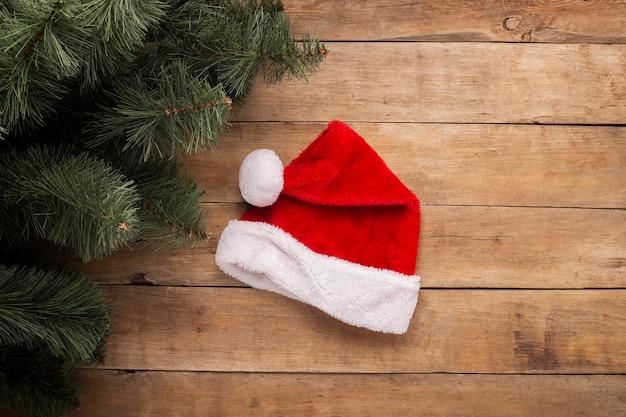 Kerstmis achtergrond. kerstman hoed en takken van een kerstboom op een houten achtergrond. bovenaanzicht, plat gelegd.
