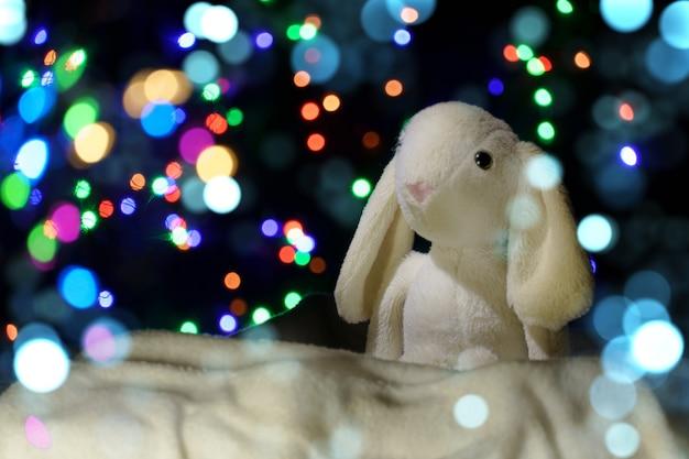 Kerstmis achtergrond. pluche haas in de sneeuw op een achtergrond van wazige lichten.