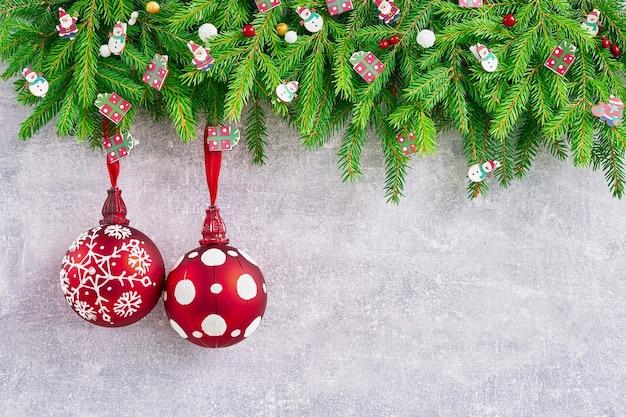 Kerstmis achtergrond. spar kerstboom met rode kerstversiering op grijze achtergrond. ruimte kopiëren. wenskaart.