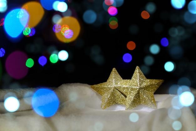 Kerstmis achtergrond. twee gouden sterren in de sneeuw op een achtergrond van intreepupil lichten.
