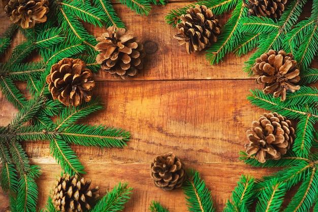 Kerstmis achtergrond. vuren takken in de vorm van een rond frame en dennenappels op een houten ondergrond