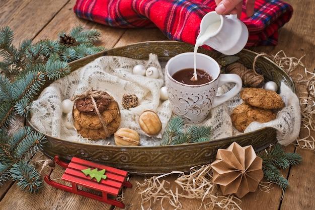 Kerstmis behandelt en decor. melk die in een mok giet
