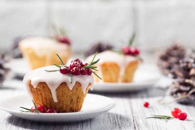 Kerstmis cupcakes met suikersuikerglazuur, amerikaanse veenbessen en rozemarijn