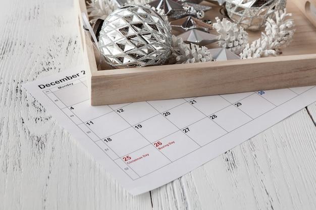 Kerstmis datum op kalender met kerst ornamenten markeren