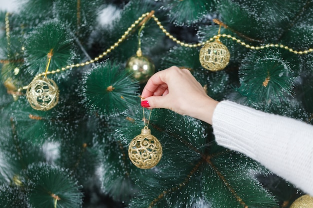 Kerstmis, de wintervakantie en mensenconcept - gelukkige jonge vrouw die kerstmisboom met bal thuis verfraaien
