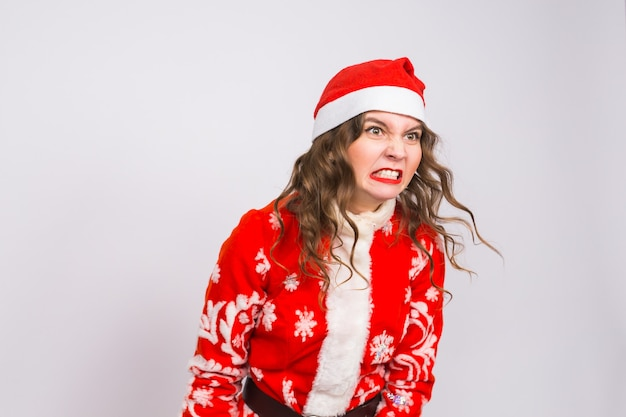 Kerstmis, emoties en mensenconcept - boze vrouw die in de kleren van de kerstman houdt stelt op witte muur voor.