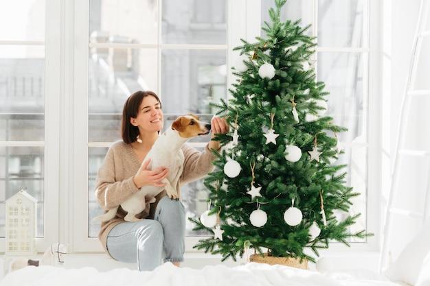 Kerstmis en feest. de gelukkige huisvrouw met brede glimlach, stelt dichtbij verfraaide spar met hond die snuisterij ruikt