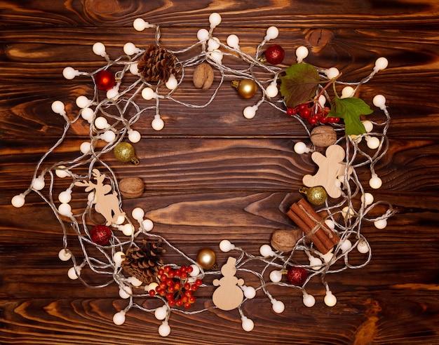 Kerstmis en gelukkig nieuwjaar op vakantie achtergrond met natuurlijke kegels, noten, houten speelgoed. kerstkaart, bokeh, vonken, gloeien. winter vakantie concept. plat lag, bovenaanzicht