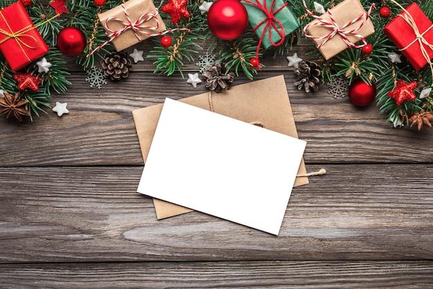 Kerstmis en gelukkig nieuwjaar wenskaart met fir tree takken, geschenkdozen, rode decoraties