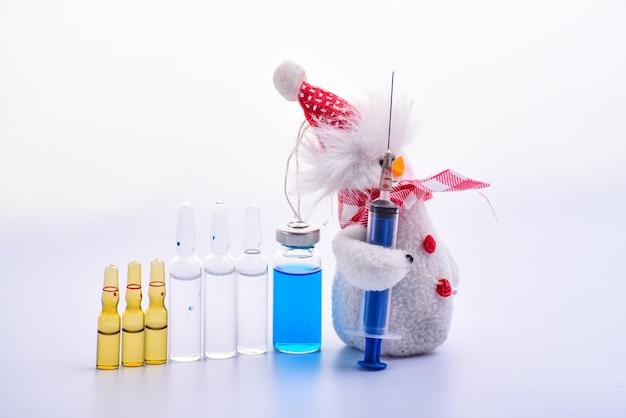 Kerstmis en medische scène een sneeuwpop die een spuit vasthoudt als een pistool en een leger van medische ampullen leidt