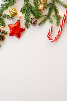 Kerstmis en nieuwjaar achtergrond concept. bovenaanzicht kerstster met dennentakken, dennenappels, speelgoed, snoepgoed en lichten op een witte achtergrond. wenskaart met kopie ruimte voor tekst en bijschriften