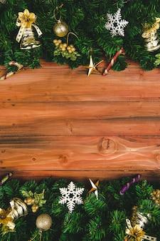 Kerstmis en nieuwjaar achtergrond, dennentakken versieren met ornamenten aan de rand, houten plank achtergrond, kopieer ruimte in het midden.