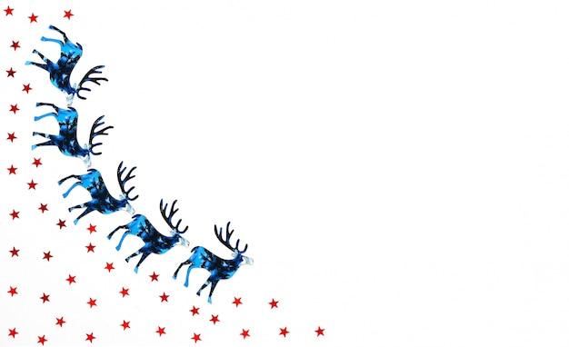 Kerstmis en nieuwjaar achtergrond met blauwe silhouet herten en rood sterren confetti.