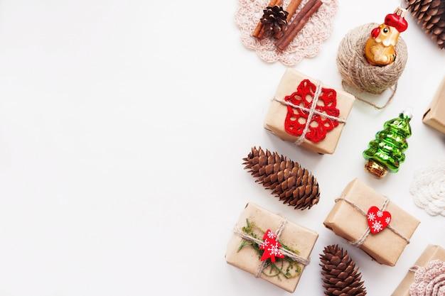 Kerstmis en nieuwjaar achtergrond met handgemaakte cadeautjes verpakt in kraft papier en decoraties.