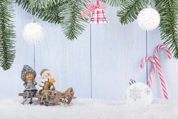 Kerstmis en nieuwjaar achtergrond met lachende beeldjes op de slee, kerstversieringen en zuurstokken
