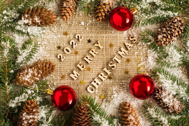 Kerstmis en nieuwjaar achtergrond op jute met de nummers van het komende jaar, vuren takken, kegels en speelgoed, rode ballen. bovenaanzicht.