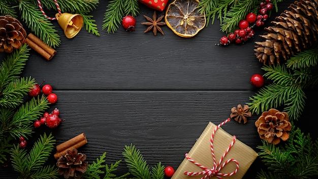 Kerstmis en nieuwjaar achtergrond. spar boomtakken en kerstversiering op zwarte houten achtergrond met kopie ruimte