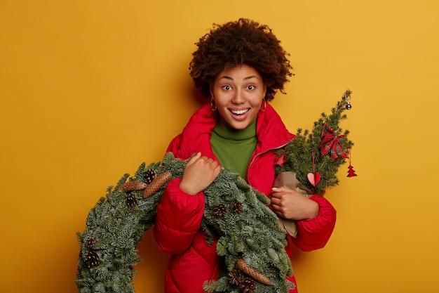 Kerstmis en nieuwjaar concept. jonge vrouw met krullend haar draagt een dennenboom en een kleine krans, maakt zich klaar voor de wintervakantie, draagt een rode jas