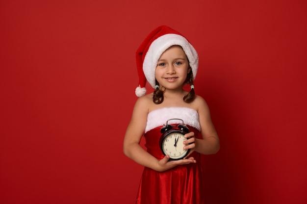 Kerstmis en nieuwjaar concept. mooi klein kind, schattig babymeisje in santa kostuum met een wekker met middernacht op gezichtsklok en kijkend naar camera tegen rode achtergrond met ruimte voor advertentie