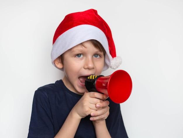Kerstmis en nieuwjaar concept. schattige kleine jongen in de kerstman afroming door megafoon