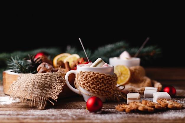 Kerstmis en nieuwjaar decor. twee kopjes met warme chocolademelk, kaneelkoekjes