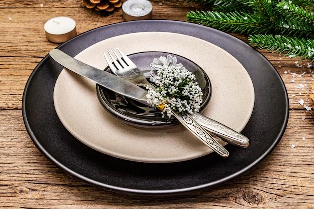 Kerstmis en nieuwjaar diner couvert. altijdgroene sparrentak, kaarsen, kegels, keramische platen, vork en mes.