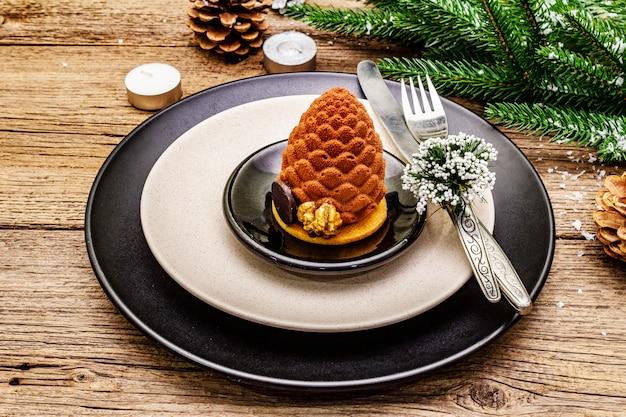 Kerstmis en nieuwjaar diner couvert. zoete snack, fir tree branch, kaarsen, kegels, keramische borden, vork en mes.