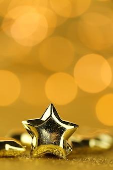 Kerstmis en nieuwjaar feestelijke achtergrond. gouden sterrenclose-up op een goud schittert achtergrond met gele bokeh.