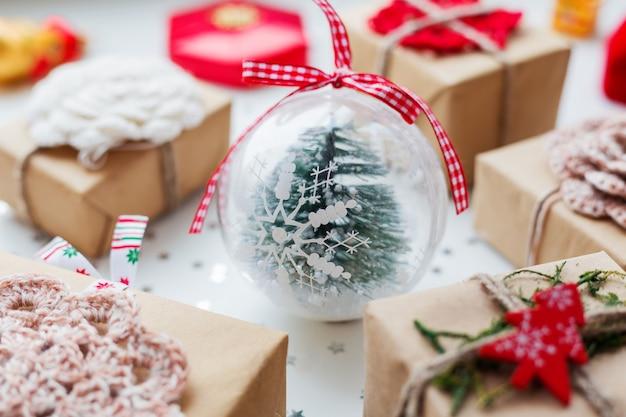 Kerstmis en nieuwjaar met cadeautjes, decoraties en decoratieve bal met spar binnen.