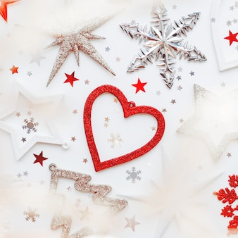 Kerstmis en nieuwjaar met sprankelende fir tree, hart, sneeuwvlokken en ster confetti. vakantiesymbolen op wit met gloeilampen.
