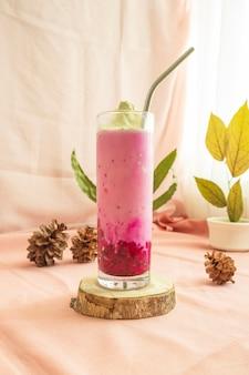 Kerstmis en nieuwjaar minimalistisch concept. de compositie geeft het product weer. dragon fruit ice milk drink met kerst- en nieuwjaarsversieringen