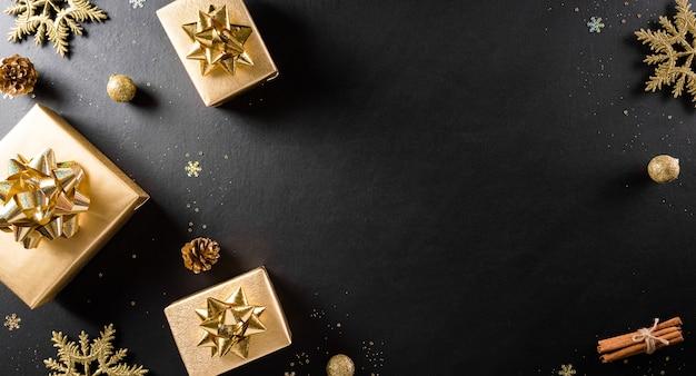Kerstmis en nieuwjaar muurconcept. bovenaanzicht van de doos van de gift van kerstmis, dennenappels, kerst bal en sneeuwvlok op zwarte houten muur.