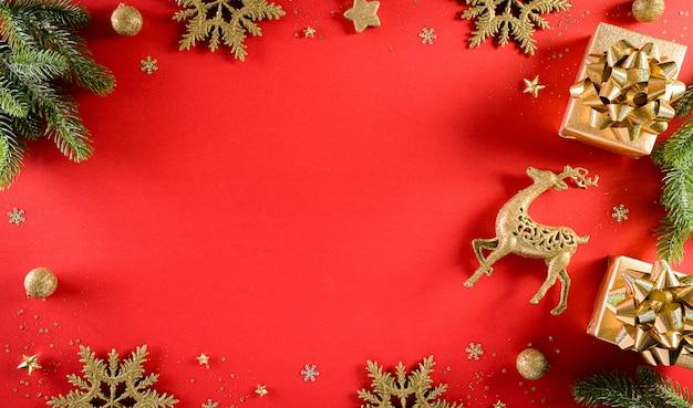 Kerstmis en nieuwjaar muurconcept. bovenaanzicht van de doos van de gift van kerstmis, vuren takken, dennenappels, rendieren, kerstbal en sneeuwvlok op rode muur.