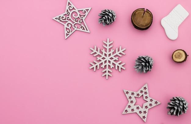 Kerstmis en nieuwjaar. roze plat lag frame met sneeuwvlokken, kerstmisspeelgoed en kegels. kopieer ruimte.