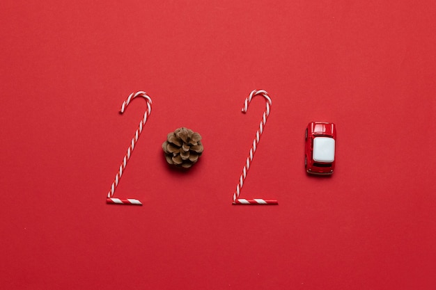Kerstmis en nieuwjaar vakantie 2020 inscriptie van verschillende versierde objecten klassieke rode glazen kerstballen bal, speelgoedauto op een rode achtergrond. horizontale rand.