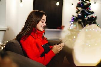 Kerstmis en Nieuwjaar vibes. Home decoraties. Charmante jonge vrouw in rode trui