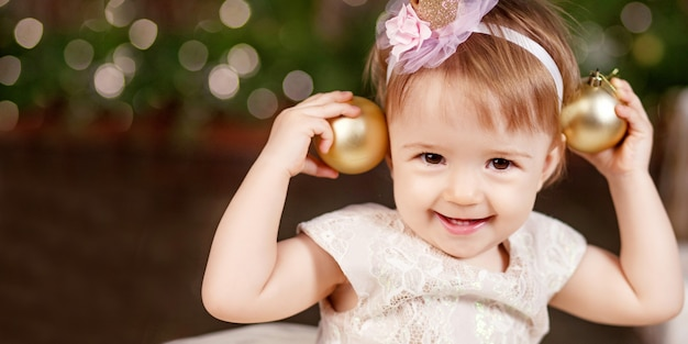 Kerstmis en nieuwjaar viering concept. mooi klein meisje in witte jurk spelen en gelukkig zijn over kerstboom en lichten