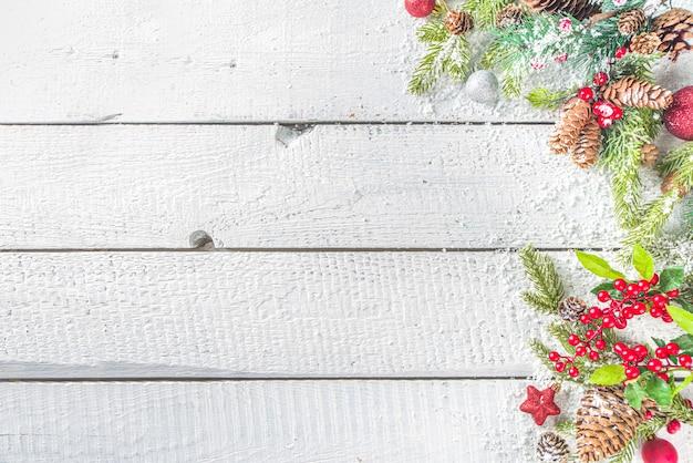 Kerstmis en nieuwjaar wenskaart achtergrond. xmas achtergrond met sparren takken, decoratie en sneeuwval op houten wit bord