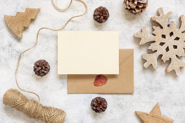 Kerstmis en nieuwjaar wenskaartsjabloon met dennenappels houten decoraties en touw op marmer