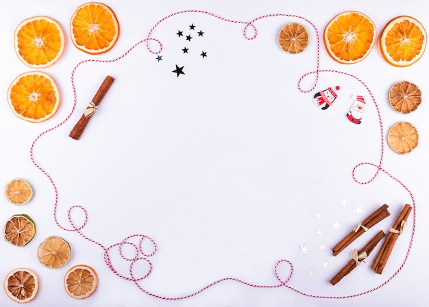 Kerstmis en nieuwjaarsamenstelling met droge sinaasappelen en kalk, lint en kruiden op witte achtergrond