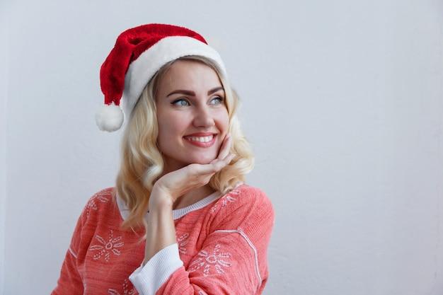Kerstmis en nieuwjaarsconcept. mooie jonge blonde vrouw in het glimlachen van het nieuwjaar. tegen een witte muur
