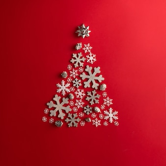 Kerstmis en oud en nieuw rode muur met kerstboom gemaakt van sneeuwvlokken. vakantie concept. plat leggen.
