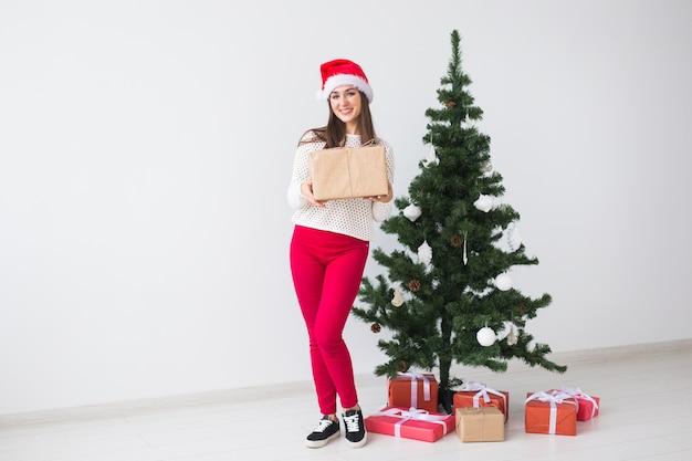 Kerstmis en vakantieconcept - vrouw in santahoed met giftdoos op witte ruimte