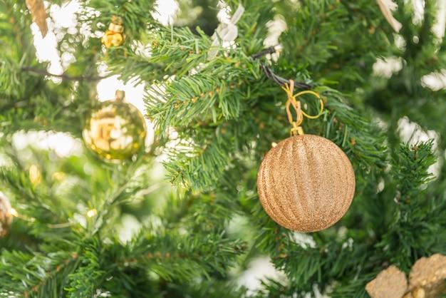 Kerstmis en vakantieseizoen concept. close-up van gouden ornament hanking op kerstboom.