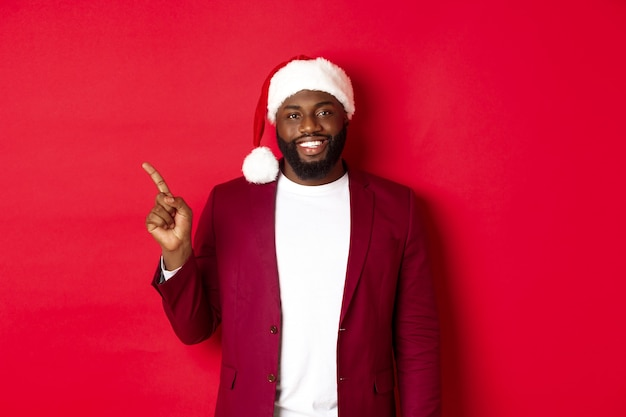 Kerstmis, feest en vakantie concept. knappe zwarte man in kerstmuts die met de vinger naar links wijst, reclame toont, gelukkig staat op rode achtergrond