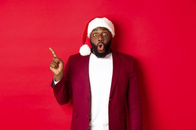 Kerstmis, feest en vakantie concept. onder de indruk zwarte man met baard, met kerstmuts, wijzende vinger naar links en hijgend verbaasd, staande tegen rode achtergrond