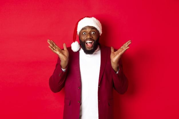 Kerstmis, feest en vakantie concept. verrast en gelukkig afro-amerikaanse man in kerstmuts, kijken met vreugde naar de camera, staande tegen rode achtergrond
