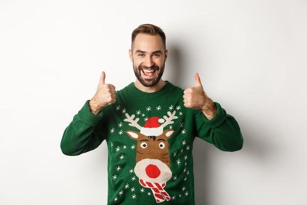 Kerstmis, feestdagen en viering. gelukkige jonge man die geniet van een nieuwjaarsfeest, duimen omhoog in goedkeuring, zoals iets goeds, staande op een witte achtergrond